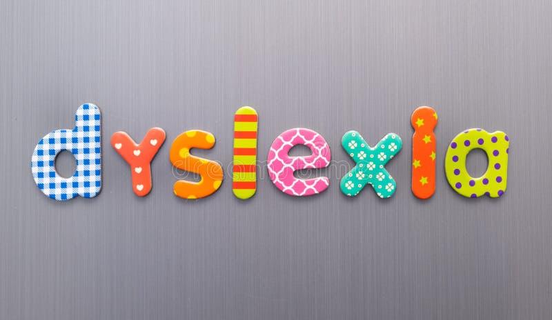 Słowo dyslexia napisane jasnymi, kolorowymi, plamistymi literami na tle szczotkowanego metalu zdjęcia royalty free