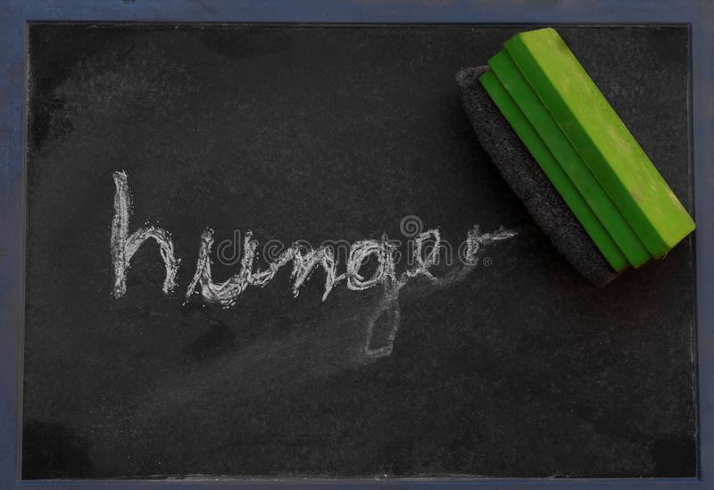 Słowo głód pisać w kredzie na blackboard wymazuje obraz stock