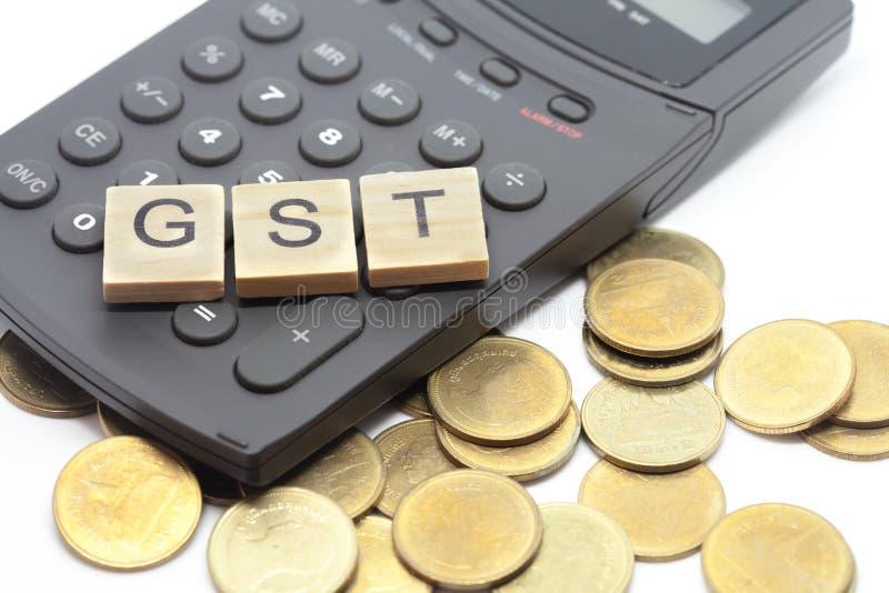 Słowo GST na drewnianych abecadło blokach na kalkulatorze fotografia stock