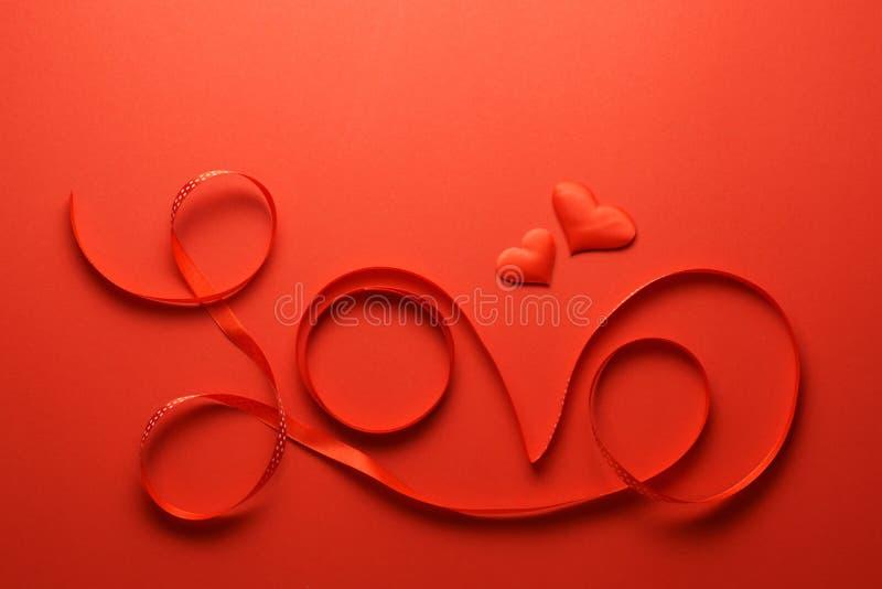Słowo miłość pisać z czerwonym faborkiem obrazy stock