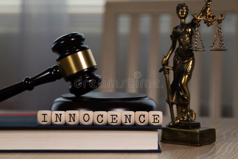 Słowo niewinność komponująca drewniany dices Drewniany młoteczek i statua Themis w tle obrazy stock