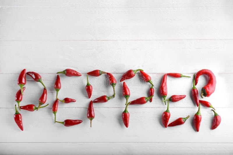 Słowo pieprz robić z czerwonym chili połuszczy na białym drewnianym tle, odgórny widok zdjęcia royalty free