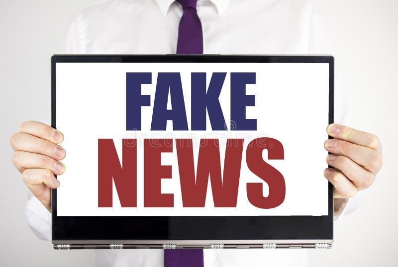 Słowo, pisze Sfałszowanej wiadomości Biznesowy pojęcie dla bajerowania dziennikarstwa Pisać na pastylka laptopu mieniu mężczyzna  zdjęcie stock