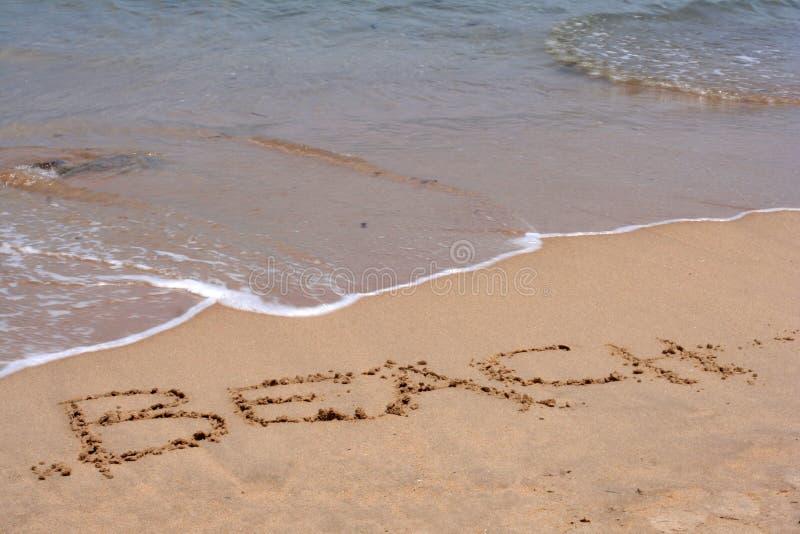 Słowo plaża pisać w piasku fotografia stock