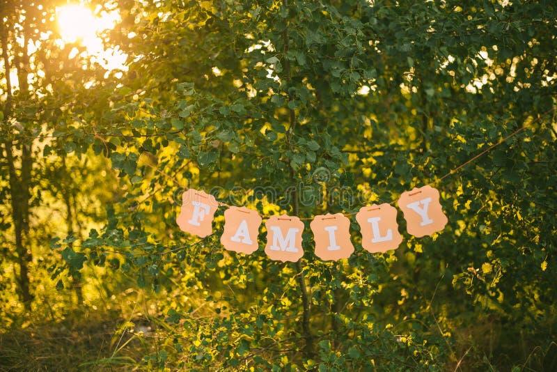 Słowo rodzina pisać na wiszącym pomarańcze papieru sztandarze obrazy royalty free