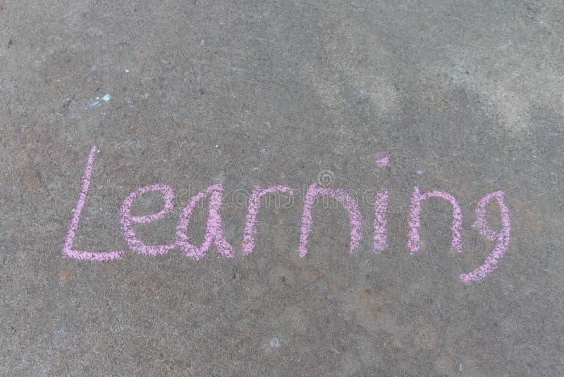 Słowo uczenie pisać z różową chodniczek kredą na szarym betonowego bruku tle zdjęcia royalty free