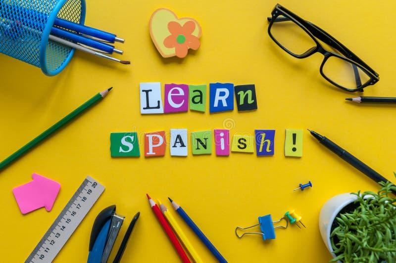 Słowo UCZY SIĘ hiszpańszczyzny robić z rzeźbiącymi listami na żółtym biurku z biurowymi lub szkolnymi dostawami, materiały Pojęci zdjęcia royalty free