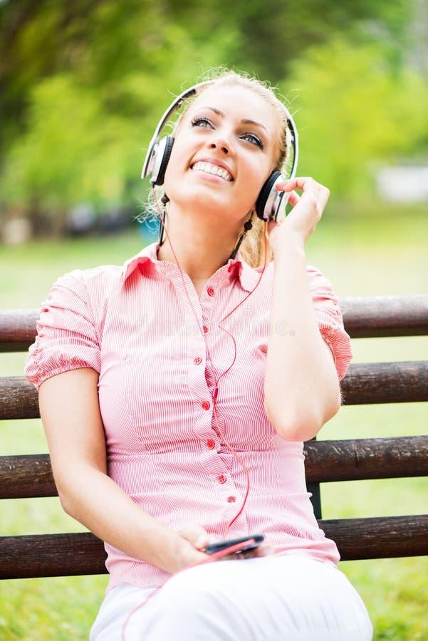 Słuchająca muzyka w parku zdjęcie stock