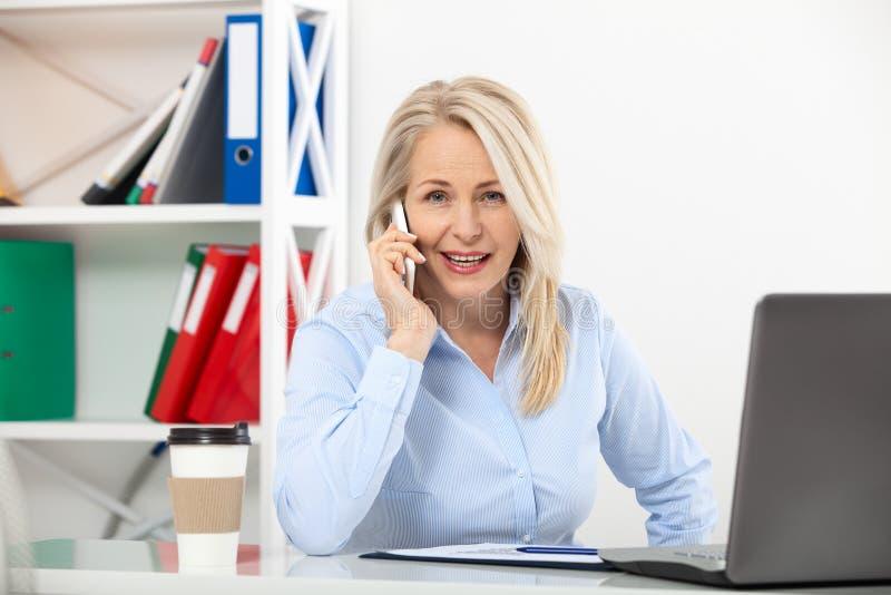 Słuchający klienci wymaganie Piękna w średnim wieku kobieta opowiada na mądrze telefonie i ono uśmiecha się przy jej pracującym m zdjęcia stock