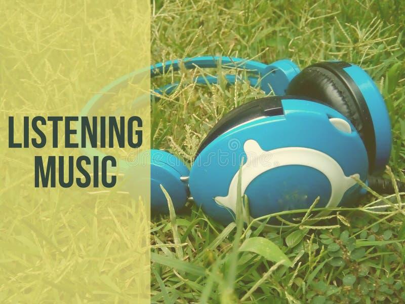 Słuchający muzyczny słowo pisać na kierowniczym telefonu tle obrazy stock