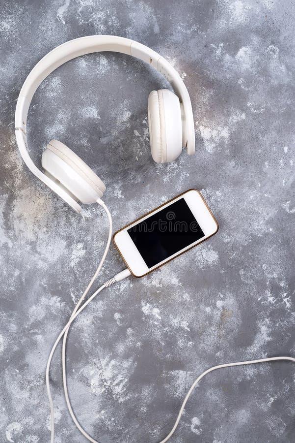 Słuchawki i telefon na kamiennym tle Przygotowywający słuchać muzyka zdjęcie stock
