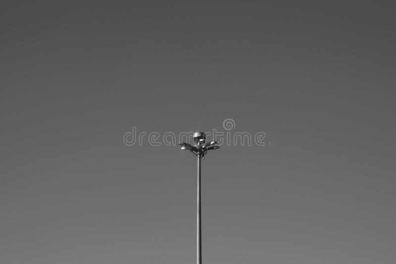 Słupek lampy ulicznej stojący samotnie na tle nieba czarno-biały obraz royalty free