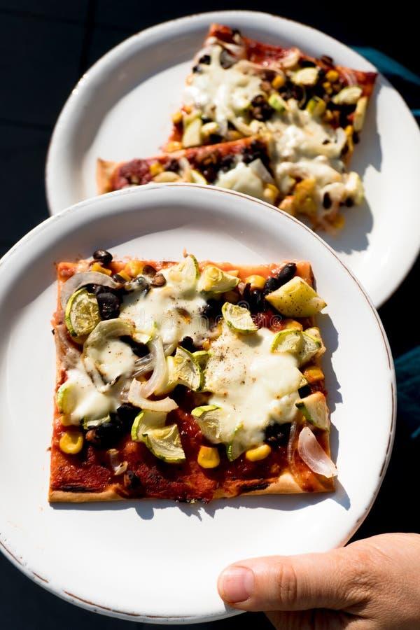Słuzyć plasterki smakowici jarscy domowej roboty pizza plasterki z świeżymi warzywami i ziele obraz royalty free