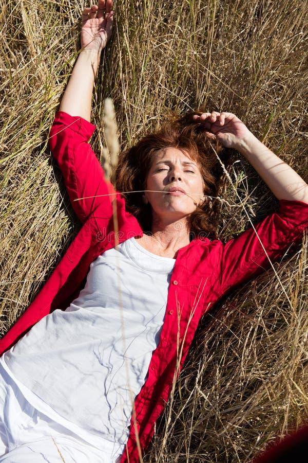 50s享受太阳温暖单独睡觉在干草的妇女 免版税库存图片
