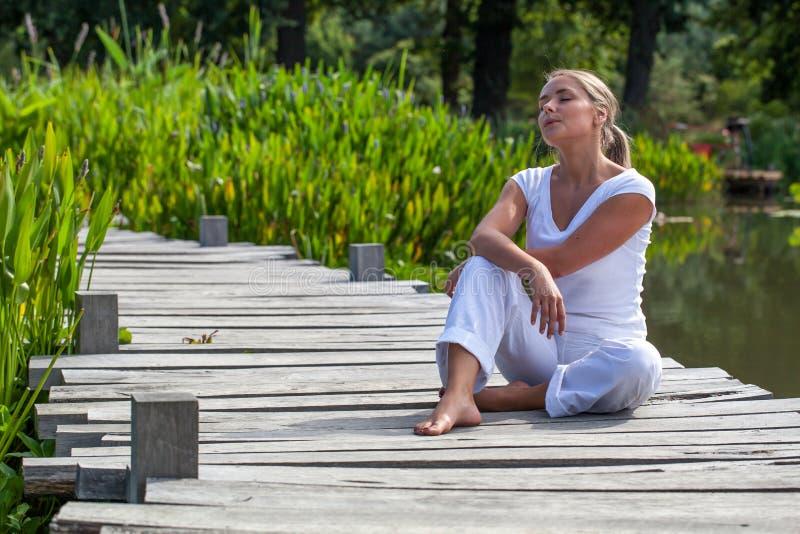 20s休息在阳光下放松的白肤金发的女孩在水附近 库存图片