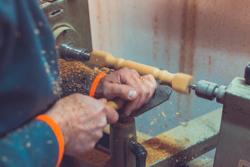 ` s手在车床附近拿着凿子的人,人工作在小木车床的,工匠使用一台手工车床,雕刻一块木头 库存图片
