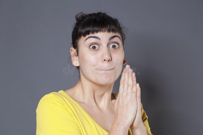 20s拿着她的嘴的深色的女孩的祈祷的概念紧 库存图片