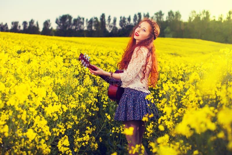 70s样式的年轻姜头发女孩与声学吉他 库存照片