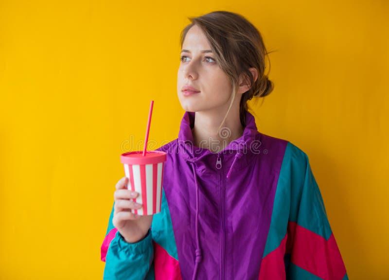 90s样式衣裳的年轻女人有杯子的 库存照片