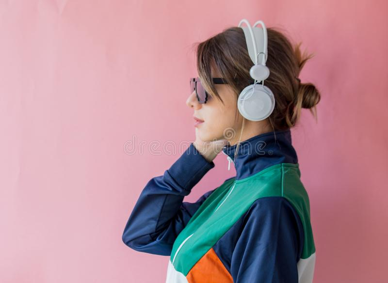 90s样式衣裳的年轻女人有耳机的 免版税库存照片