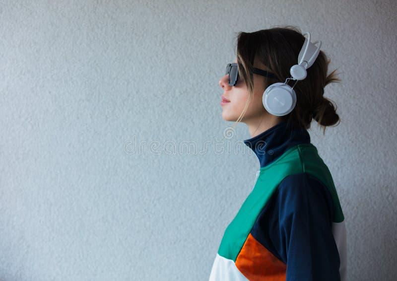 90s样式衣裳的年轻女人有耳机的 库存图片