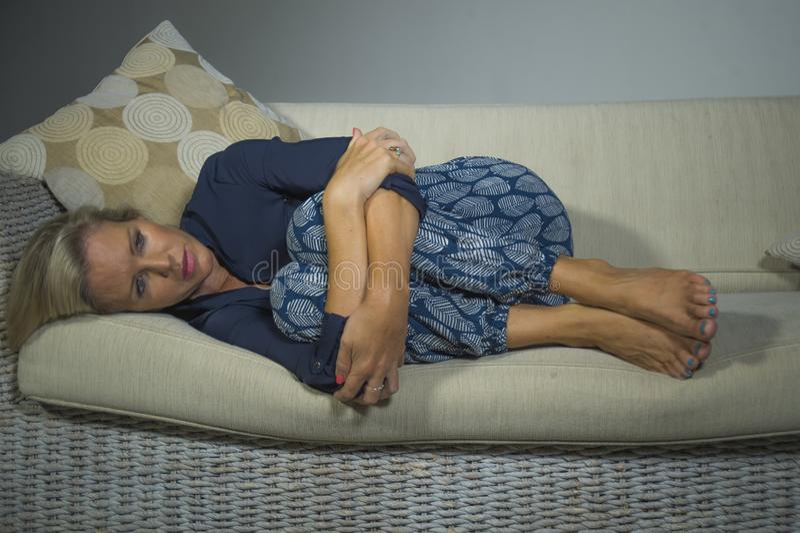 40s沮丧的和急切美丽的白肤金发的妇女感觉被挫败的在家说谎的遭受的消沉和忧虑问题沙发co 库存图片