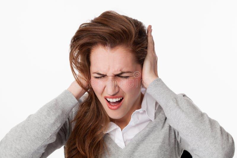 20s生气对耳鸣问题或大声的音乐的妇女 库存图片