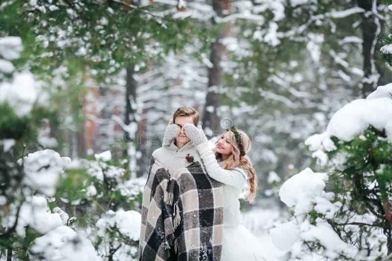 ` s由她注视的逗人喜爱的女孩覆盖物男朋友编织了mittes 户外婚姻冬天的新娘新郎 附庸风雅 库存图片