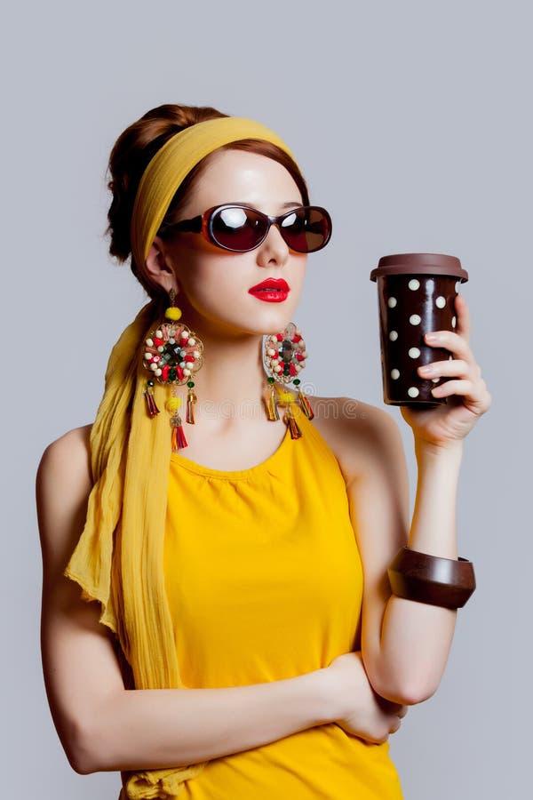 70s的女孩给与咖啡杯的样式穿衣 免版税库存图片