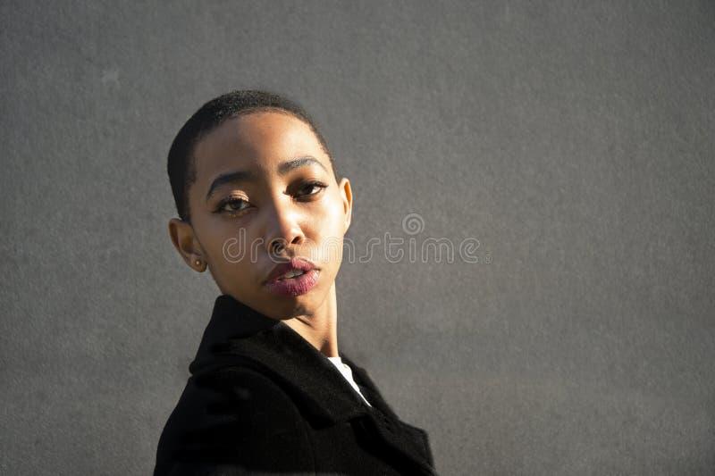 20s皮肤头头发的年轻非洲黑人妇女画象在自然光有灰色墙壁背景 库存照片