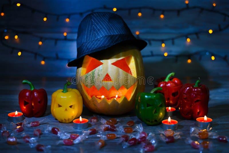 ` S Ève de Halloween la Jack-o-lanterne dans un chapeau et des bougies à l'intérieur, effrayant le visage allume grightening bleu photos stock