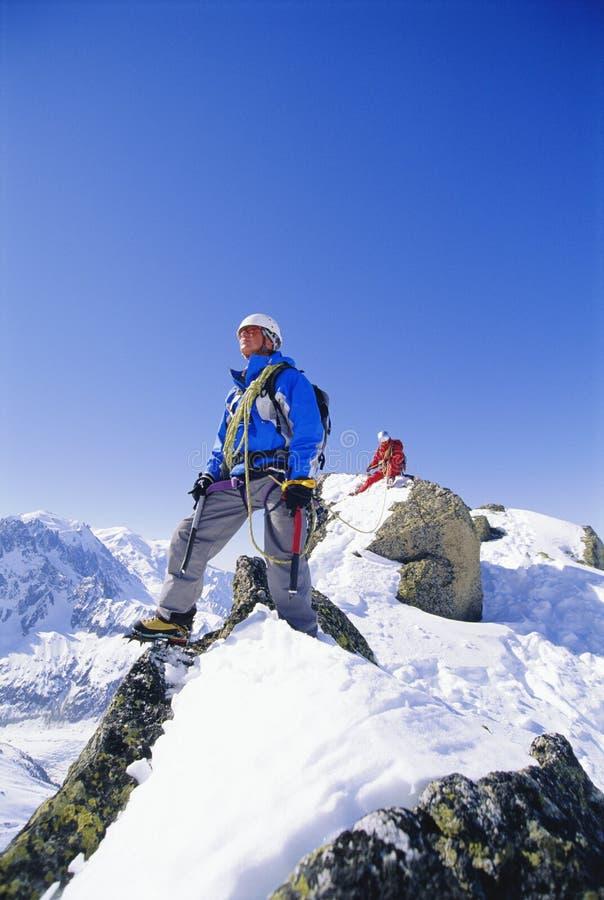 S'élever de montagne de jeunes hommes sur la crête neigeuse images stock