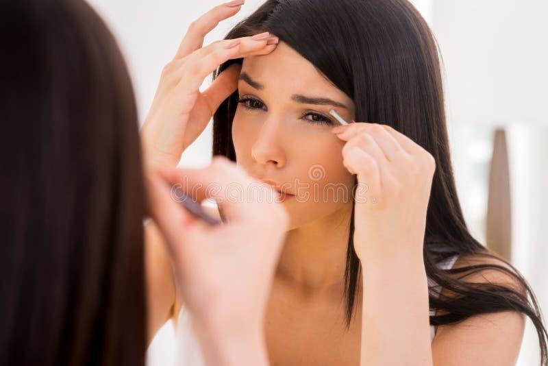 S'épiler des sourcils photo stock