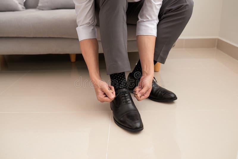 Ανθρώπινα χέρια που δένουν το κορδόνι των νέων παπουτσιών του πόδι και χέρια ατόμων που δένουν τις δαντέλλες παπουτσιών στοκ εικόνες