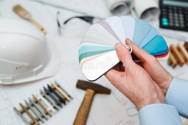 ` S архитектора внутреннее вручает чертежу домашнюю иллюстрацию с материальным образцом, концепцию реновации стоковое изображение