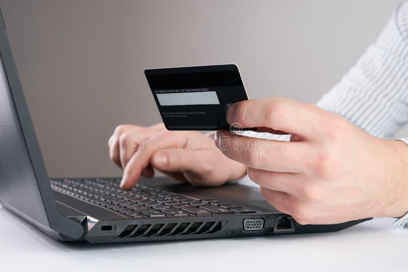 ` S бизнесмена вручает держать кредитную карточку и использование компьтер-книжки стоковое изображение rf