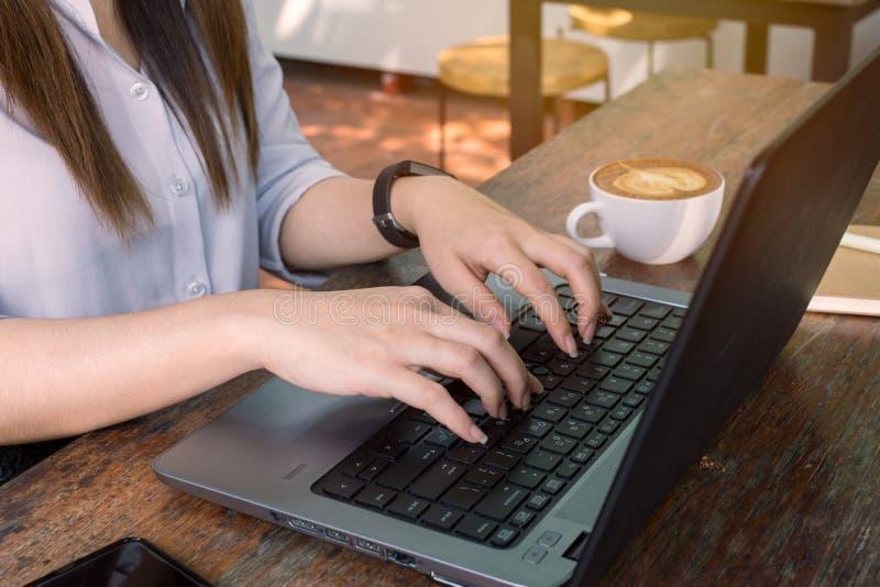 ` S бизнес-леди вручает работу и печатать на клавиатуре компьтер-книжки на деревянном столе стоковое изображение