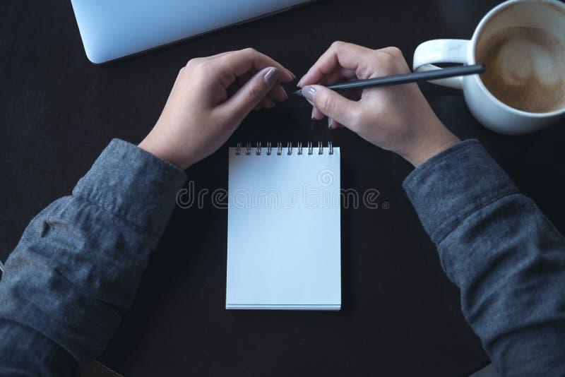 ` S женщины вручает держать карандаш к записи на пустой тетради с компьтер-книжкой и кофейной чашкой на таблице стоковые фотографии rf