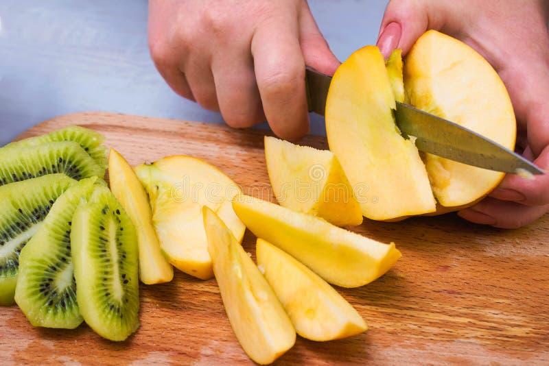 ` S женщины вручает отрезать яблоко и киви стоковое изображение