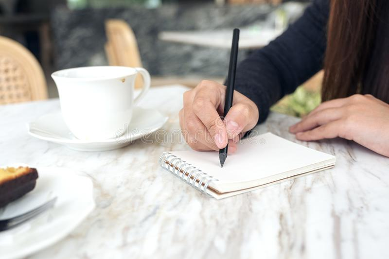 ` S женщины вручает писать вниз на белой пустой тетради с кофейной чашкой и десертом на таблице в кафе стоковое изображение rf