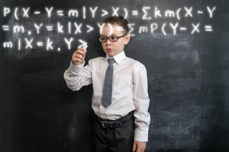 ` S молодого парня писать длинную формулу ` s математики задняя школа принципиальной схемы к увеличенная реальность Умный и ухищр стоковая фотография rf