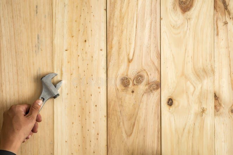 ` S работника вручает держать универсальный гаечный ключ готовый зафиксировать что-то стоковое изображение rf