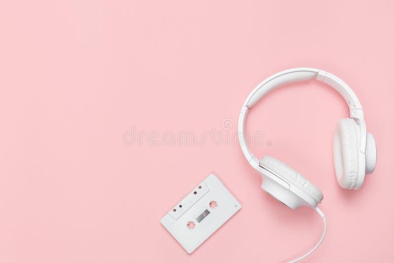 Белые кассета и наушники на розовой предпосылке стоковое изображение rf