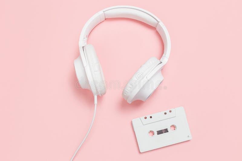 Белые кассета и наушники на розовой предпосылке стоковое изображение