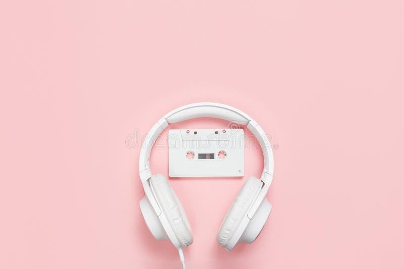 Белые кассета и наушники на розовой предпосылке стоковая фотография