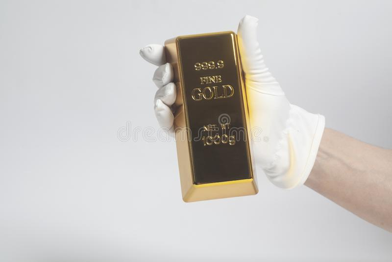 在拿着金锭的白色手套的人的手 免版税库存照片
