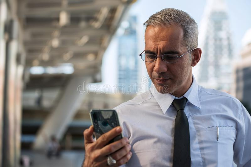 50s American businessman check smartphone in city royalty free stock images