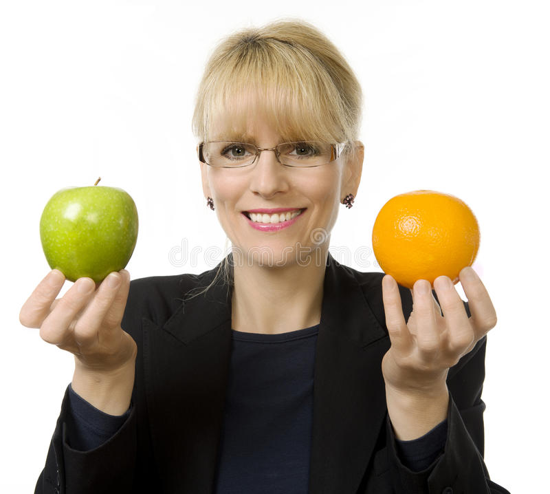 Its apples and oranges!. A woman holds and apple and an orange stock photos