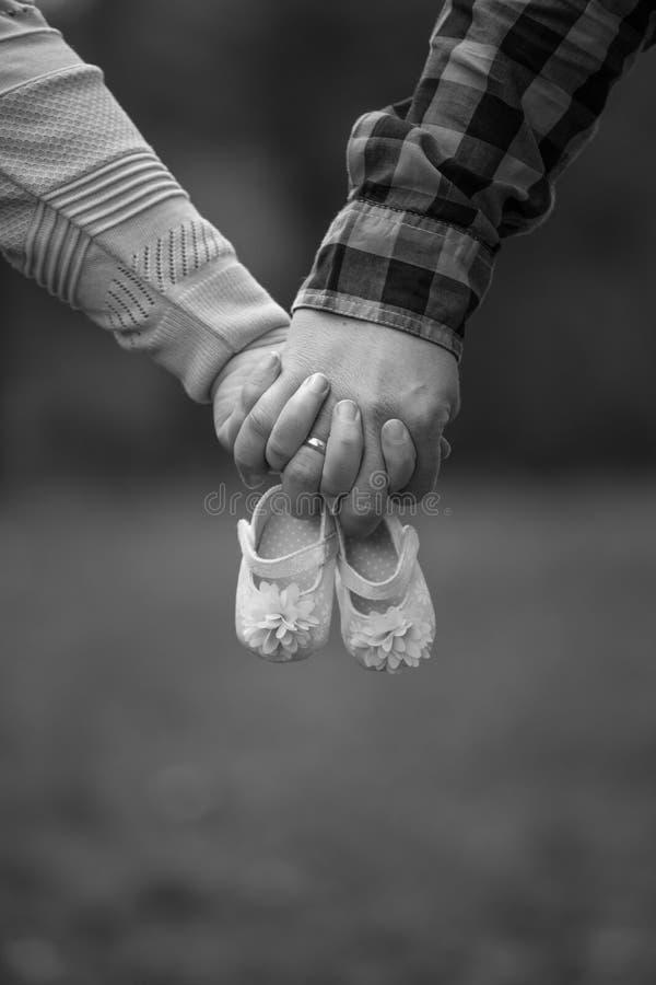 S'attendant à des parents jugeant des chaussures de bébé disponibles image libre de droits