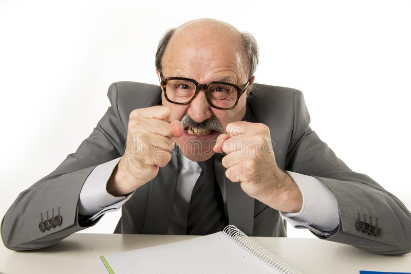 60s bald senior office boss man furious and angry gesturing upset and mad sitting on desk with paperwork in business and job prob stock images